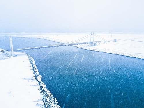 snow aerial view of bridge coat snow over body of water winter