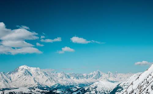 mountain aerial view of snow covered mountains sky