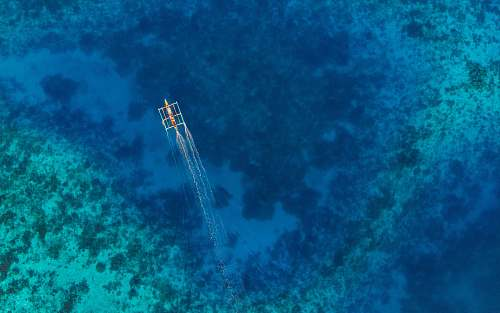 nature aerial-view photography of boat on sea water