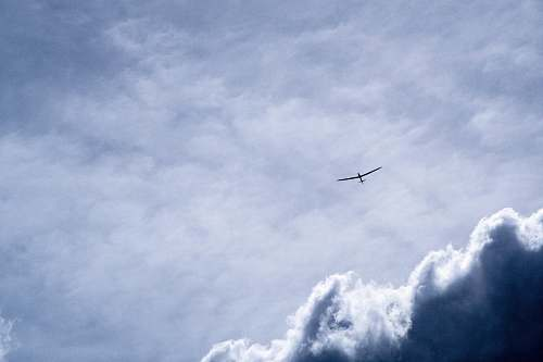 sky bird flying through white clouds airplane