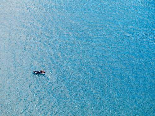 ocean bird's eye view photography of boat on body of water sea