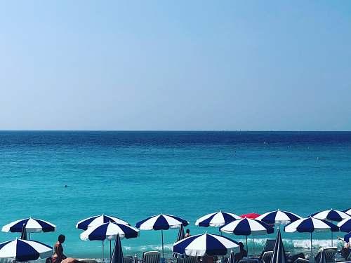 human blue and white patio umbrella near at seashore person
