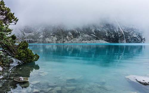 glacier blue body of water surrounded by trees mountain