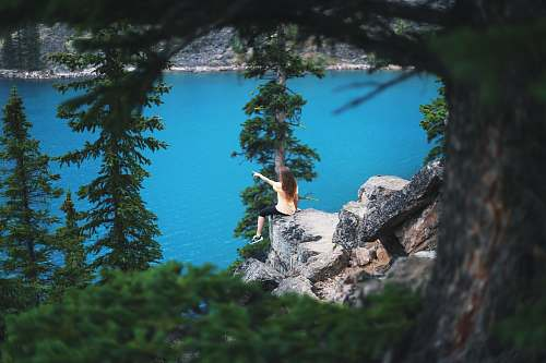 tree girl sitting on cliff near trees pointing towards body of water landscape