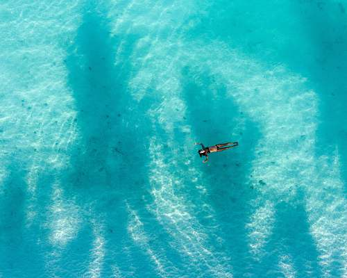 unnamed road high angle photography of woman swimming during daytime huraa