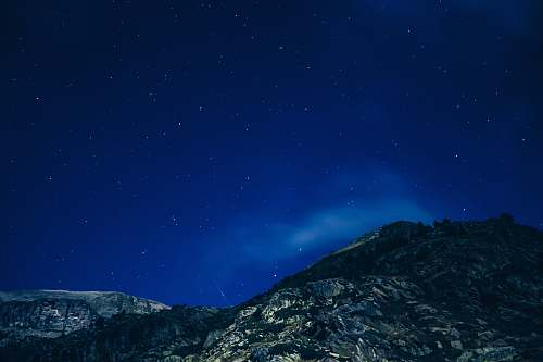 stars low angle photography of mountain during nighttime rock