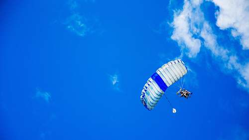 parachute low-angle photography of person riding fan-powered chair with parachute up in sky sky