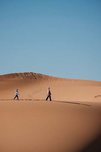 desert man and woman walking on brown sands dune