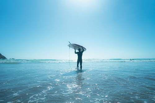 ocean man holds surfboard on water sea