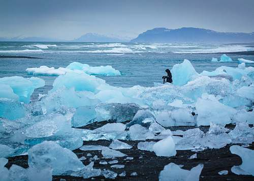 glacier man standing in middle of ice burg ice