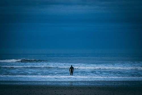 ocean man standing on beach under cloudy sky sea