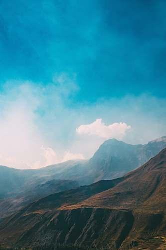 mountain mountain view under blue sky mist