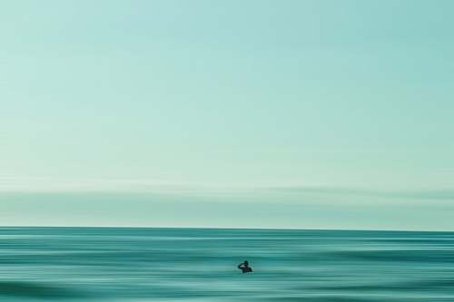 water person in middle of ocean during daytime horizon