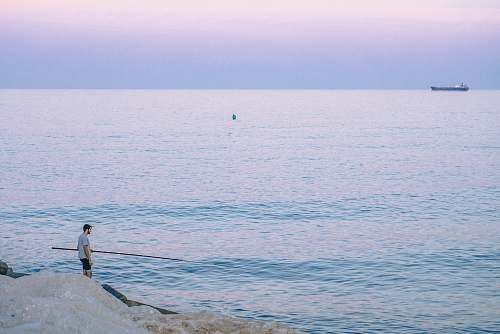 sea person standing on rock holding stick facing body of water during golden hour man