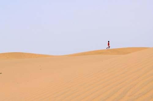 sand person walking on desert desert