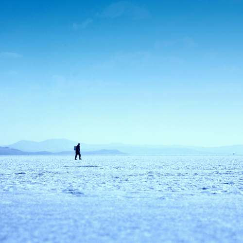 nature person walking on ice field photo sky