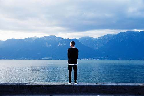 lake person wearing black pants and top standing on wall clouds