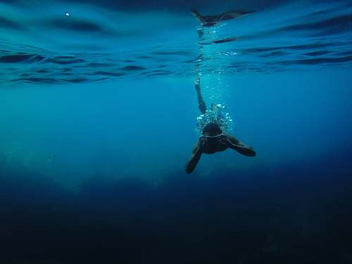 underwater person wearing goggles while swimming under body of water ocean