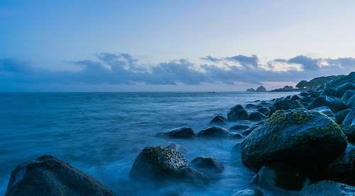 ocean rocks near calm sea under blue sky promontory