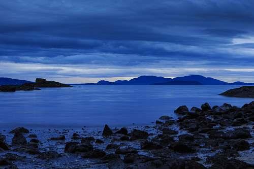sea rocks on seashore under gray clouds coast