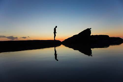 nature silhouette of man standing on land near body of water with reflection laguna beach