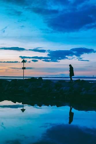 water silhouette of person walking on rocks near body of water reflection