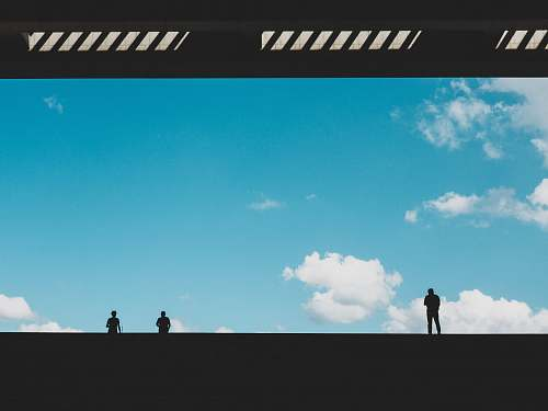 building silhouette of three person against blue sky landing page