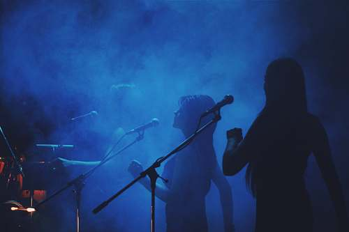music silhouette photography of three women standing in front of microphone stands diver