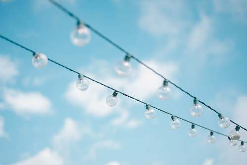 person tilt lens photography of string lights under cloudy skies human