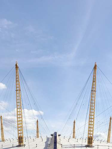 london two yellow cable towers under blue sky the o2 arena