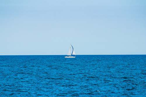 boat white sailboat in the middle of the ocean during day transportation