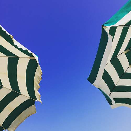 cushion worm's-eye view photography of two green and white patio umbrella under blue sky during daytime home decor