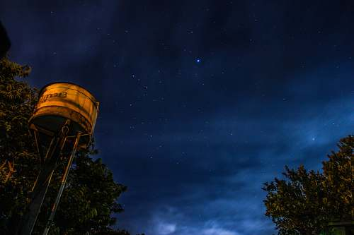 water tower worm's-eye view photography of white steel tank beside green tree under starry sky tree