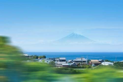 blue timelapse photo of house near ocean across Mt. Fuji sea