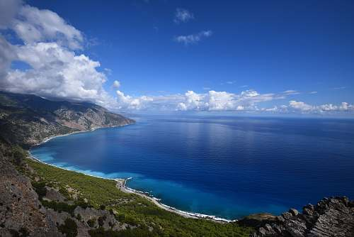 water blue ocean water beside mountain under blue and white cloudy sky ocean