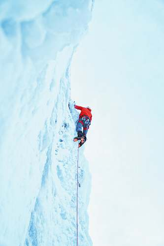 brown person wearing red jacket climbing on glacier red