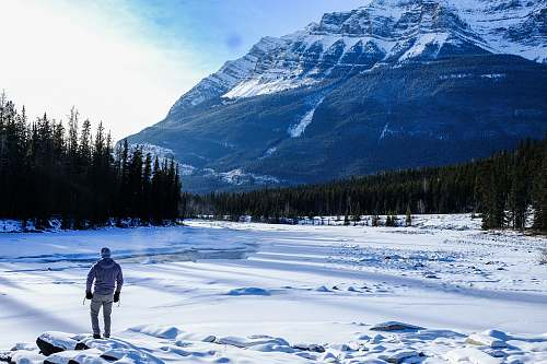 blue person standing on snow near mountain during daytime snow
