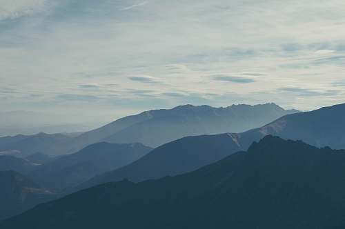 grey silhouette of mountains covered with fog mountain range