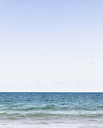 blue calm sea under clear blue sky during daytime ocean