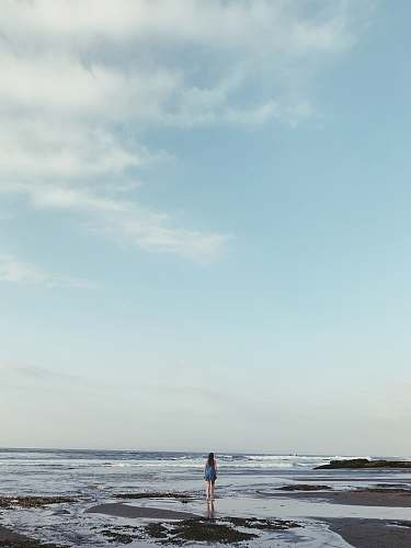 blue landscape photo of a woman on a beach outdoors