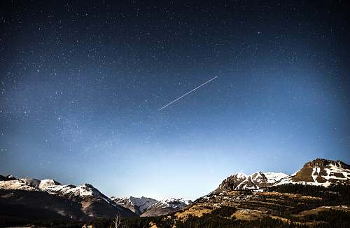 mountain photo of shooting star over snow covered mountains sky