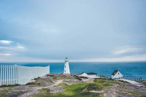 lighthouse lighthouse on cliff near fence and house coast