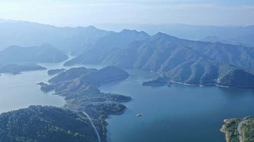 nature aerial photography of body of water viewing mountain under blue and white sky land