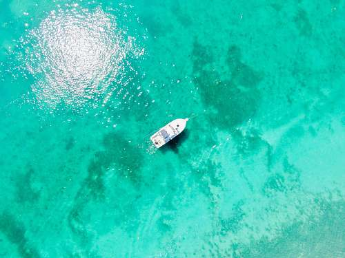 nature aerial photography of white boat in body of water during daytime water
