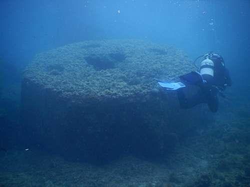 water man diving underwater near round structure person