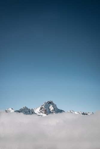 mountain selective focus photography of white mountain under blue calm sky alps