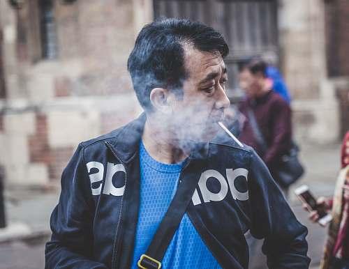 human man in black Adidas leather jacket smoking cigarette people