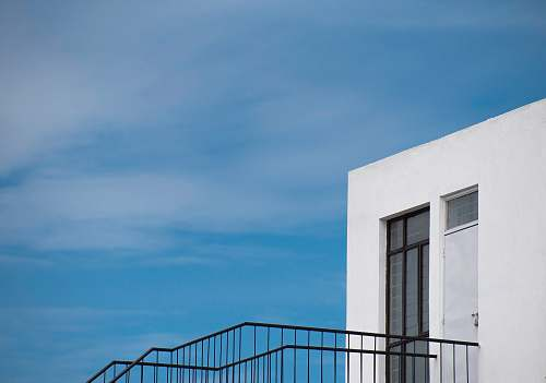 banister white building with black staircase under blue sky handrail