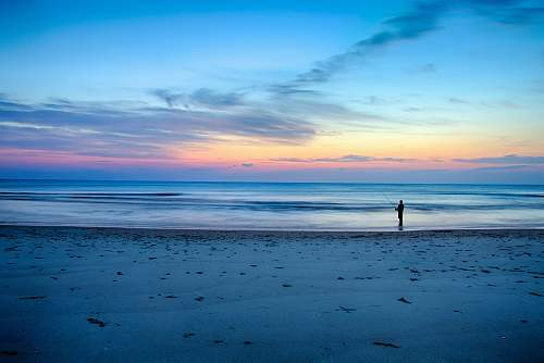 ocean silhouette of person fishing on shallow part of sea beach