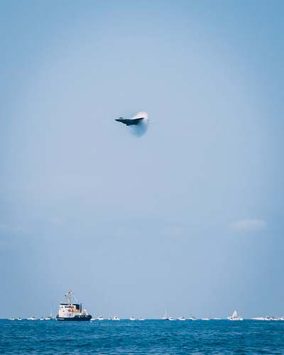 vehicle jet fighter creating sonic boom over the sea with ships boat
